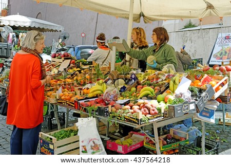 Rome, Italy - May , 17.2016 - A customer in front of  a fruit and vegetable stall at outdoor market
