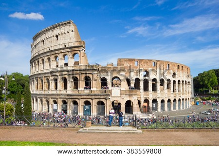 ROME, ITALY - MAY 2, 2015 : People walking in front of the Colosseum. The famous arena is the symbol of Imperial Rome and is visited by thousands of tourists every year.