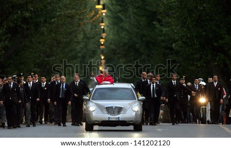 ROME, ITALY - MAY 07 - Pope Benedict XVI waves to pilgrims in his car, escorted by bodyguards, on his way to St. Mary Major Basilica in Rome, Italy on May 7, 2005. - stock photo