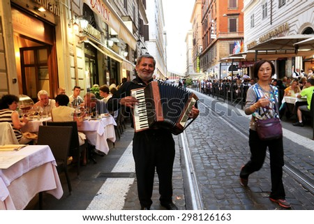 ROME, ITALY - MAY 18th 2015.A street musician with accordion near the cafe with tourists, Rome, Italy