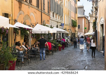 ROME, ITALY - MAY 27, 2016: Tourists and restaurants on a street in the city center. - stock photo