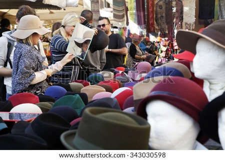 ROME, ITALY - NOVEMBER 07 2015: Woman trying a wool hat looking in a mirror  on stall at outdoor market in Rome, Italy