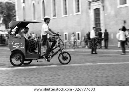 ROME, ITALY - OCTOBER 03 2015: Tourists in a rickshaw. Unidentified people ride cycle rickshaw in Rome, Italy