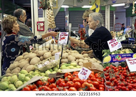 ROME, ITALY - 24 SEPTEMBER 2015: A customer, left, pays for her purchase from a fruit and vegetable stall inside an indoor market in Rome, Italy