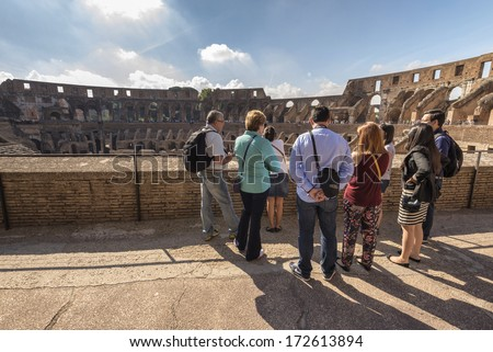 ROME, ITALY - SEPTEMBER 25 : Interior of Colosseum ; tourist group listens guided tour on September 25, 2013 in Rome Italy. - stock photo