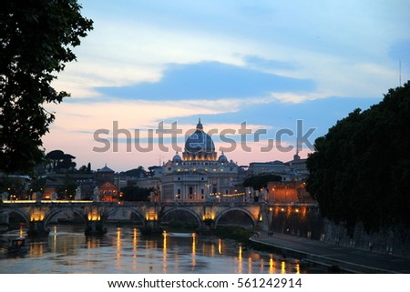 Rome, Italy. The sunset view on a river, a bridge and a cathedral.