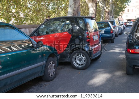 ROME - NOV 2: Smart car on a parking near Tiber River, November 2, 2012 in Rome. The capital is the city with the major number of Smarts in Italy, thanks to their parking versatility - stock photo
