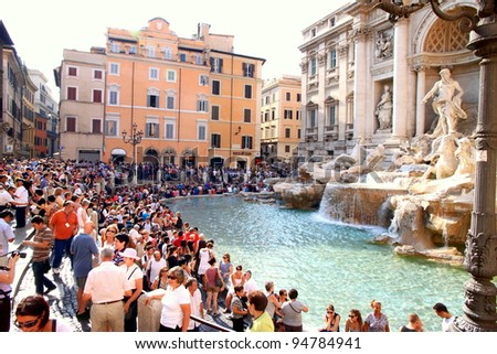 ROME - SEPTEMBER 18: Tourists visiting the Trevi Fountain on September 18, 2011 in Rome. Trevi Fountain is among the most iconic fountains in the world and one of Italy's top tourism destinations. - stock photo