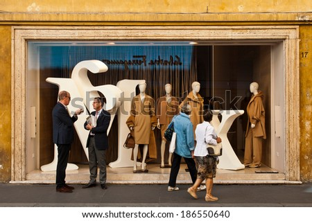 ROME - SEPTEMBER 18: unidentified men talking and women looking at Max Mara show window at Via dei Condotti in Rome, Italy on September 18, 2013. MaxMara had 2,254 stores in 90 countries by March 2008 - stock photo