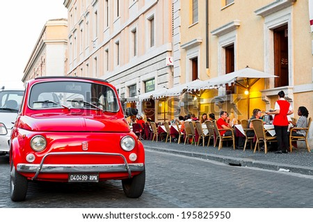 ROME - SEPTEMBER 21: vintage Fiat 500 parked next to a restaurant esplanade in Via della Conciliazione on September 21, 2013 in Rome, Italy. The world famous Italian automobile brand founded in 1899. - stock photo