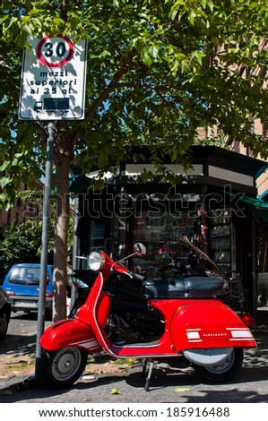 ROME - SEPTEMBER 23: Vintage Vespa parked on the street next to a typical kiosk in Rome, Italy on September 23, 2013. - stock photo