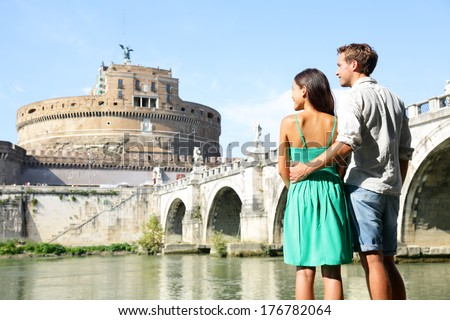 Rome travel tourists by Castel Sant'Angelo. Happy romantic couple looking at the roman castle enjoying their romantic summer holidays travel in Italy, Europe. Man and woman embracing. - stock photo