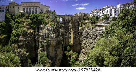 """Ronda Panoramic view over Puente Nuevo (""""New Bridge"""") The newest and largest of three bridges that span the 120-metre deep chasm that carries Guadalevin River and divides the city. Southern Spain. - stock photo"""