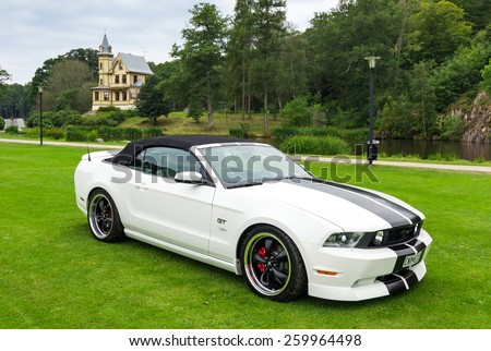 "RONNEBY, SWEDEN - AUGUST 09: Summer V8 car fans event ""Pony & muscle car meet"". Front and side view of Ford Mustang model 2010 in 08 August, 2014 in Ronneby, Sweden. - stock photo"
