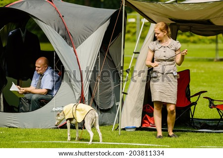 RONNEBY, SWEDEN - JULY 06, 2014: Blekinge Kennelklubb international dog show. Female handler walking a whippet with protective sheet over back.
