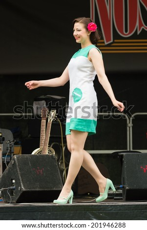 RONNEBY, SWEDEN - JUNE 28, 2014: Nostalgia Festival, classic cars, motorcycles, fashion and entertainment. Fashion show retro style. White and green dress.