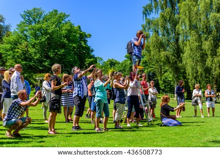 Ronneby, Sweden - June 6, 2016: The Swedish national day celebration in public park. Lots of people taking photographs when the school orchestra lined up for a photo opportunity.