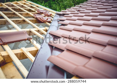 Roof building at new house construction. Brown roof tiles covering estate - stock photo
