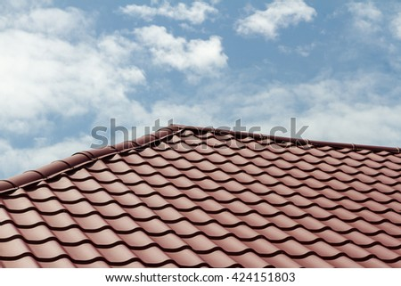 roof covered with metal tile in red against the sky