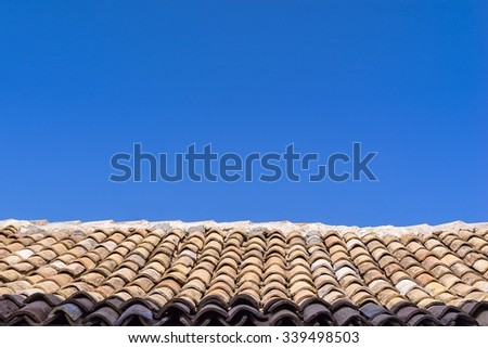 roof from an old tile against a blue clear sky
