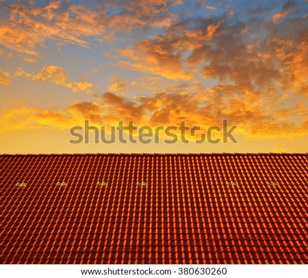Roof house with tiled roof at sunset - stock photo