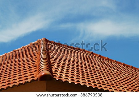 Roof house with tiled roof on blue sky.        - stock photo
