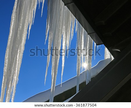 Roof icicles formed from snow on blue sky background - stock photo
