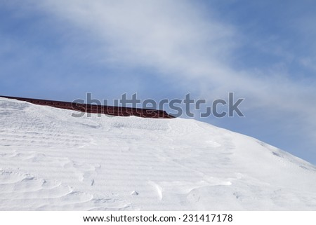 Roof in snow and blue sky - stock photo