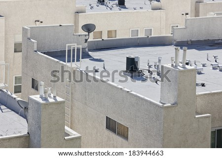 Roof is flat with air conditioners on top of a modern apartment.