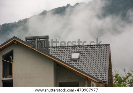 Roof of new house with skylight and chimney over foggy mountain