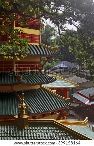 Roof of the Chinese style pagoda temple of the goddess Guanyin, a small monkey sitting next to roof decoration, Krabi Town, Thailand - stock photo