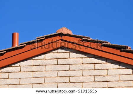 roof of the house on the blue sky background - stock photo