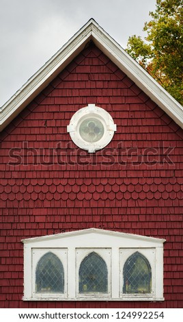 Roof point of an old red building in New England.