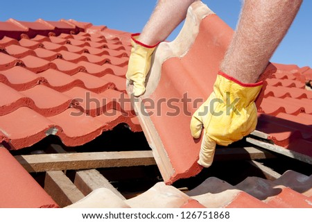 Roof repairs, worker with yellow gloves replacing red tiles or shingles on house with blue sky as background and copy space. - stock photo
