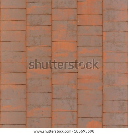 Roof texture containing flat, red shingles with worn surfaces. - stock photo