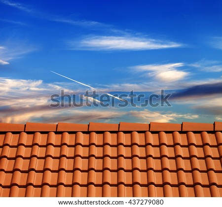 Roof tiles in evening and sky with sunlight clouds - stock photo