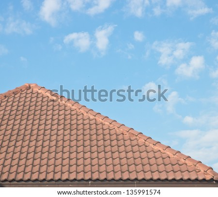 Roof tiles under blue sky - stock photo