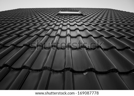 Roof tiles with a small window in Black and White - stock photo