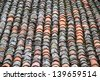 Roof with old clay tiles red and full of mosses and lichens - stock photo
