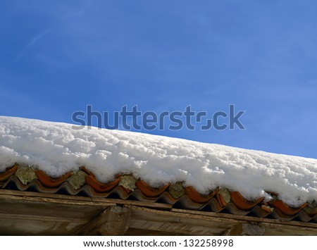 roof with snow on blue sky background - stock photo