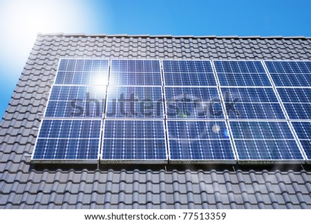 Roof with solar panels fragment under sunny blue sky - stock photo
