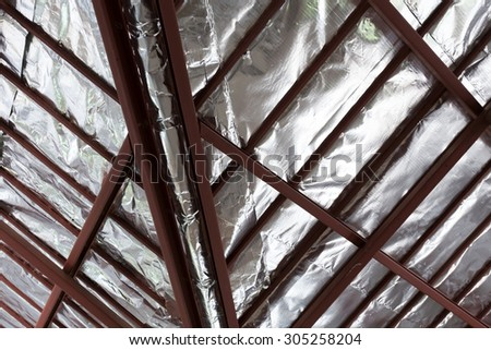 roof with steel beam and silver foil insulation heat on ceiling roof house - stock photo