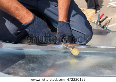 Roofer builder worker finishing folding a metal sheet using rubber mallet