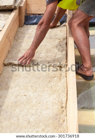 Roofer builder worker installing roof insulation material - stock photo