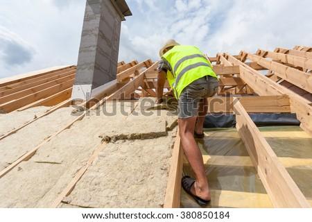 Perfect Roofer Builder Worker Installing Roof Insulation Material On New House  Under Construction