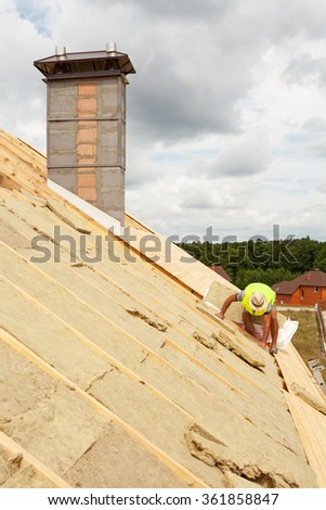 Roofer builder worker installing roof insulation material (rockwool) on new house under construction