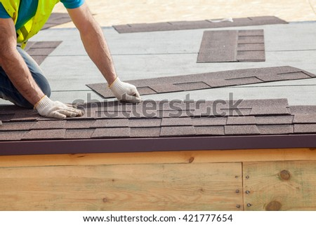 Roofer builder worker installing roof shingles  - stock photo