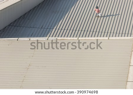 roofer builder worker with colour spraying paint on metal sheet roof - stock photo