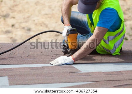 Roofer builder worker with nailgun installing Asphalt Shingles or Bitumen Tiles on a new house under construction - stock photo