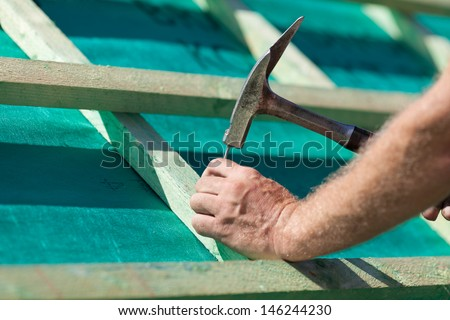Roofer hammering a nail into the new roof beams - stock photo